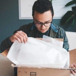Junger Mann öffnet ein Geschenk